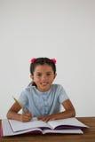 Młodej dziewczyny writing w jej książce przeciw białemu tłu Fotografia Royalty Free