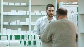 Młodej farmaceuty i starszego mężczyzna klient z lekiem i recepta przy apteką Obrazy Stock