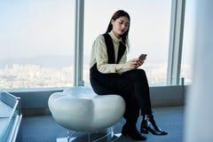 Młodej Japońskiej kobiety dumny CEO sprawdza emaila w sieci przez mądrze telefonu obrazy stock