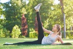 Młodej kobiety ćwiczy joga outdoors przy parkiem Fotografia Stock