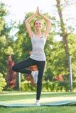 Młodej kobiety ćwiczy joga outdoors przy parkiem Zdjęcie Royalty Free
