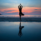 Młodej kobiety ćwiczy joga przy zmierzchem na wybrzeżu Zdjęcia Royalty Free