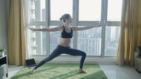 Młodej kobiety ćwiczy joga z pejzażu miejskiego tłem w domu