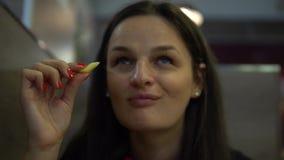 Młodej Kobiety łasowania francuza dłoniaki w restauraci blisko twarz zbiory wideo