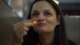 Młodej Kobiety łasowania francuza dłoniaki w restauraci blisko twarz zbiory