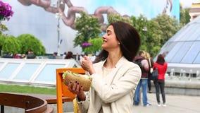 Młodej kobiety łasowania kanapka w outdoors kawiarni zdjęcie wideo
