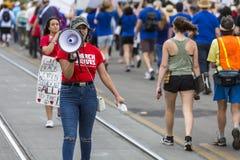 Młodej kobiety adresowania tłum z megafonem przy napad z bronią w ręku prot Zdjęcie Royalty Free