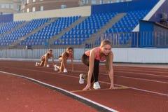 Młodej kobiety atleta przy zaczyna pozycją przygotowywającą zaczynać rasy Fotografia Stock
