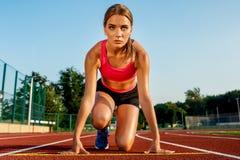 Młodej kobiety atleta przy zaczyna pozycją przygotowywającą zaczynać rasy na torze wyścigów konnych Obraz Stock
