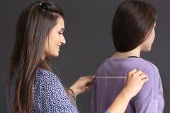 Młodej kobiety bierze klienta krawieccy pomiary w atelier obrazy stock
