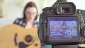 Młodej kobiety blogger, siedzi na leżance bawić się gitara strzał przez kamera ekranu