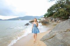 Młodej kobiety chodzić bosy na piasku, ranku denny brzeg fotografia stock