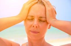 Młodej kobiety cierpienie z migreną Kobieta na gorącej plaży z sunstroke Problem zdrowotny na wakacje Obrazy Royalty Free