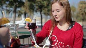 Młodej kobiety clink szkła z chłopakiem w ulicznej kawiarni zbiory wideo