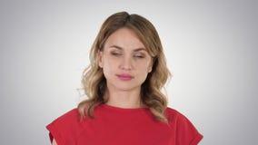 Młodej kobiety czerwona koszulka chodzi, patrzejący kamerę na gradientowym tle zbiory