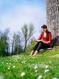 Młodej kobiety czytanie i cieszyć się wiosna Obraz Royalty Free