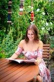 Młodej kobiety czytanie w pustym magazynie podczas gdy siedzący w gar fotografia stock