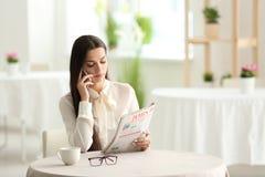 Młodej kobiety czytelnicza gazeta podczas gdy opowiadający na telefonie komórkowym w kawiarni obrazy stock