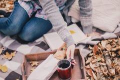 Młodej kobiety czytelnicza książka i pić herbata w lesie Fotografia Stock