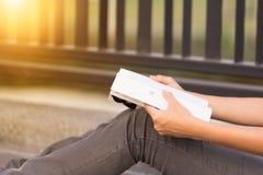 Młodej kobiety czytelnicza książka w ona ręki fotografia stock