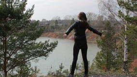 Młodej kobiety dźwigania ręki stoi na jeziornym brzeg cieszy się wiatrową piękną naturę zbiory