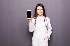 Młodej kobiety doktorski pokazuje telefon komórkowy przeciw popielatemu tłu obrazy stock