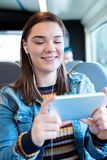 Młodej Kobiety dopatrywania film Na telefonie komórkowym Podczas podróży Wor zdjęcia royalty free