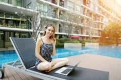 Młodej kobiety dopatrywania film z laptopu komputerem osobistym outdoors daleko jako freelancer blisko do pływackiego basenu i bu zdjęcia stock
