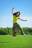 Młodej kobiety doskakiwanie na zielonej łące zdjęcie stock