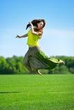 Młodej kobiety doskakiwanie na zielonej łące obrazy stock