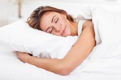 Młodej kobiety dosypianie na białej pościeli w łóżku przy Zdjęcie Stock