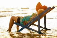 Młodej kobiety dosypianie na plażowym krześle przy zmierzchem Obraz Stock