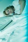 Młodej kobiety dosypianie w łóżku przy nocą zdjęcie royalty free