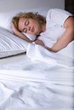 Młodej kobiety dosypianie w łóżku przy nocą Zdjęcie Stock