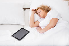 Młodej kobiety dosypianie w łóżku z pastylka pecetem Fotografia Royalty Free