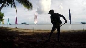 Młodej kobiety działanie jako plaży cleaner grabienia ściółki, gruzy na tropikalnej piaskowatej plaży zdjęcie wideo