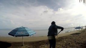 Młodej kobiety działanie jako plaży cleaner grabienia ściółki, gruzy na tropikalnej piaskowatej plaży zbiory wideo