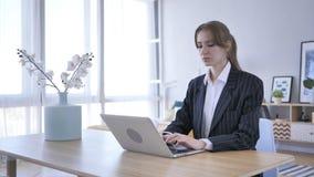 Młodej Kobiety działanie, Pisać na maszynie Na laptopie w biurze obraz royalty free