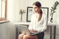 Młodej kobiety freelancer indoors ministerstwa spraw wewnętrznych pojęcia formalny stylowy siedzący pisać na maszynie fotografia stock