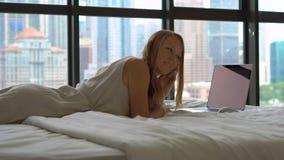 Młodej kobiety freelancer pracuje na jej laptopu lying on the beach na łóżku bierze hełmofony daleko i gdy słucha rozmowę telefon zdjęcie wideo