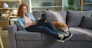 Młodej kobiety freelancer pracuje z laptopu pisać na maszynie siedzieć na kanapie z ślicznym psem zbiory wideo