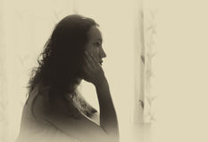 Młodej kobiety główkowanie blisko jaskrawego okno i obsiadanie zaświecamy czarny i biały filtrujący wizerunek obrazy royalty free
