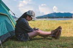 Młodej kobiety gadki ogólnospołeczni środki smartphone out campingowym namiotem Zdjęcia Stock