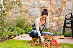 Młodej kobiety grabienia liści jesieni stosu weranda Zdjęcie Stock