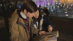 Młodej kobiety i mężczyzna gmerania ulica na papierowej mapie, turyści gubjący w cudzoziemskim mieście zbiory