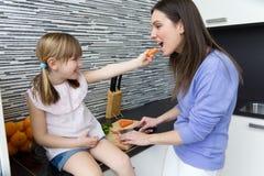 Młodej kobiety i małej dziewczynki łasowania marchewki w kuchni Fotografia Royalty Free