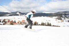 Młodej Kobiety jazda na snowboardzie na skłon zimy mroźnym dniu Obrazy Royalty Free