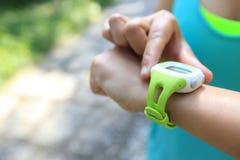 Młodej kobiety jogger przygotowywający bieg set i patrzeć sporta mądrze zegarek obrazy stock