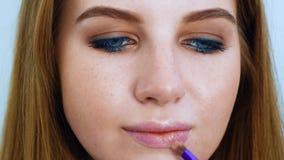 Młodej kobiety kładzenia wargi glosa z makeup muśnięcia zbliżeniem zbiory