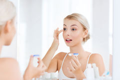 Młodej kobiety kładzenie na szkłach kontaktowych przy łazienką zdjęcia stock